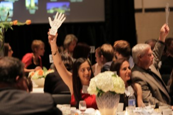 """Attorney Anita Fox and her daughter get in the action raising their """"bid hand"""" during the auction."""