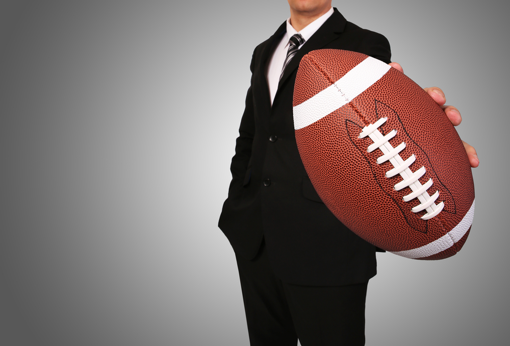 Photo of a businessman or attorney holding a football.